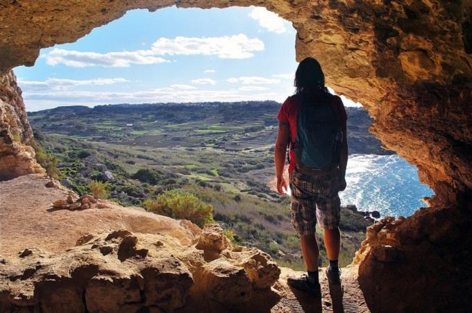 man in cave looking at ramla bay